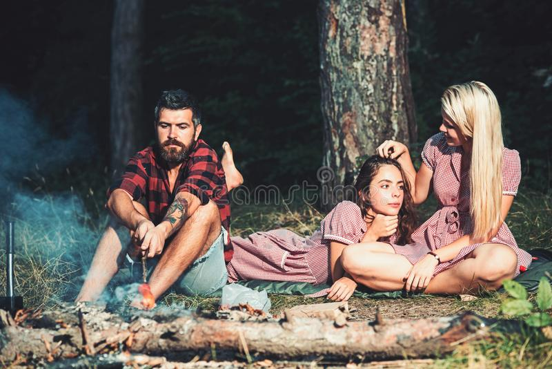 Bearded man roast sausage for women in vintage dresses. Hipster and girls relax at bonfire in forest. Boyfriend cook royalty free stock photos