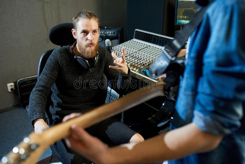 Sound producer talking to musician in studio stock photos