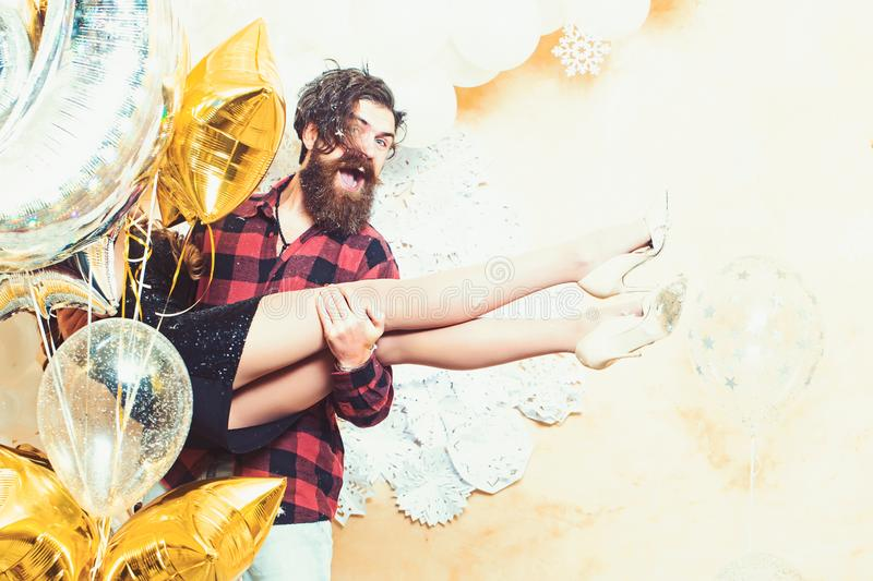 Bearded man smile with woman in hands on christmas. Hipster and woman on new year or xmas eve. Couple in love enjoy stock photography