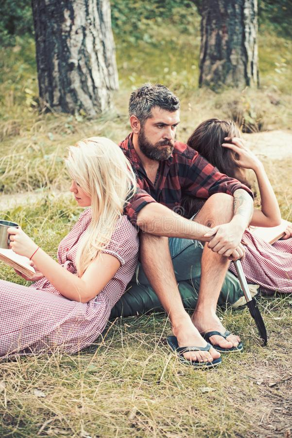 Bearded man with women in forest. Hipster with tourist shovel and women read books. Friends camping on nature. People. Bearded men with women in forest. Hipster stock photography