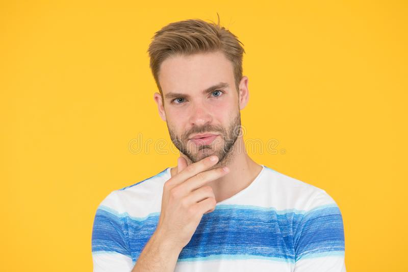 Bearded moderately. Bearded man on yellow background. Unshaven guy touching his bearded chin. Handsome caucasian model stock photos
