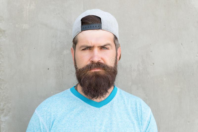 Bearded and moustached. Bearded man on grey wall. Serious bearded hipster in casual summer style. Caucasian guy wearing. Long mustache and beard hair on bearded stock photos