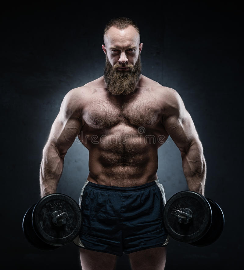 Bearded Muscular bodybuilder posing with heavy dumbbells. On grunge background royalty free stock photo