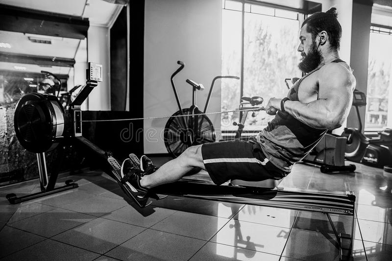 Muscular fit man using rowing machine at gym royalty free stock images