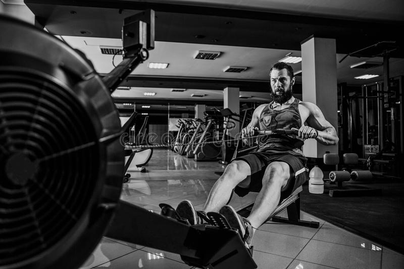 Muscular fit man using rowing machine at gym stock photos