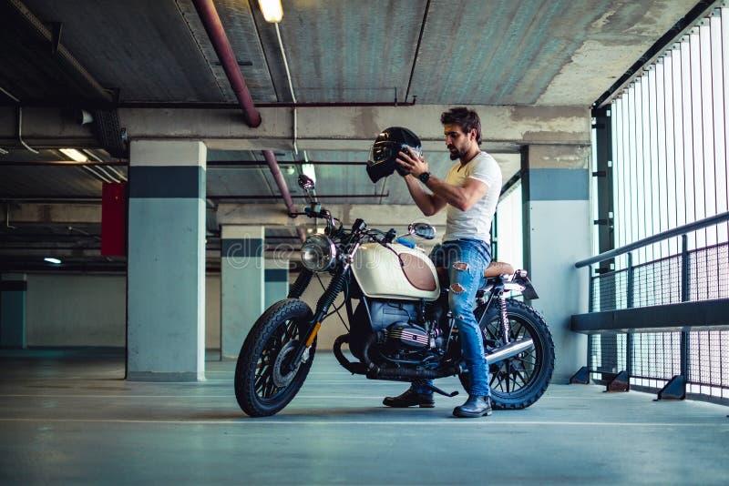Man putting on motorcycle helmet in a garage stock image