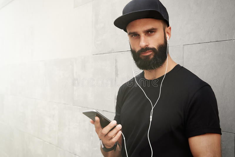 Bearded Muscular Man Wearing Black Tshirt Blank Snapback Cap Summer Time.Young Men Smiling Opposite Empty Gray Concrete. Wall Background Using Smartphone royalty free stock images