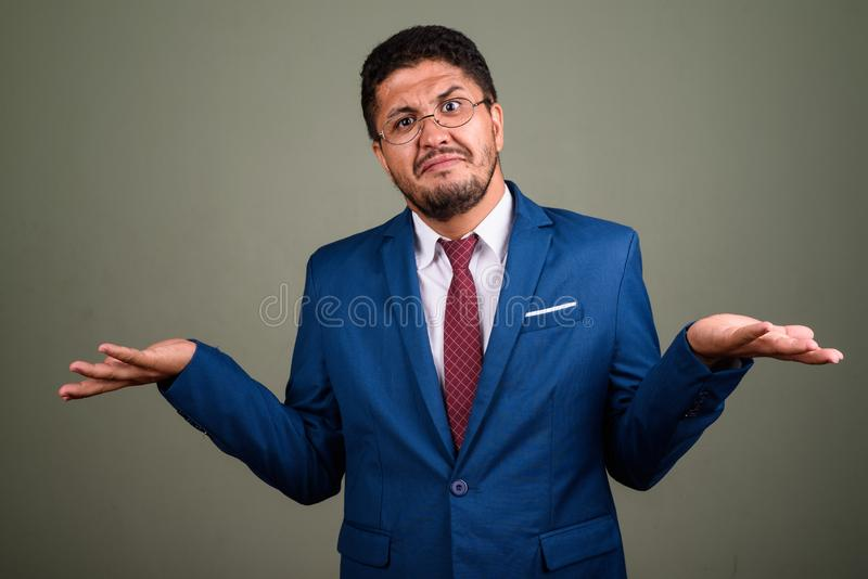 Bearded Persian businessman wearing suit against colored backgro. Studio shot of bearded Persian businessman wearing suit against colored background stock images