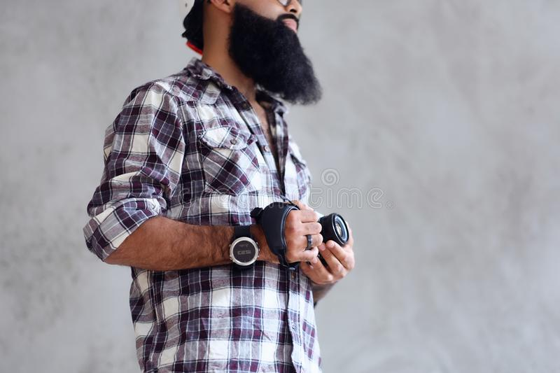 Bearded photographer holds compact DSLR camera over grey background. royalty free stock photography