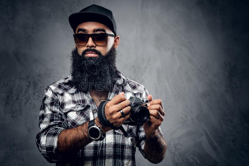 Bearded photographer holds compact DSLR camera over grey background. stock image
