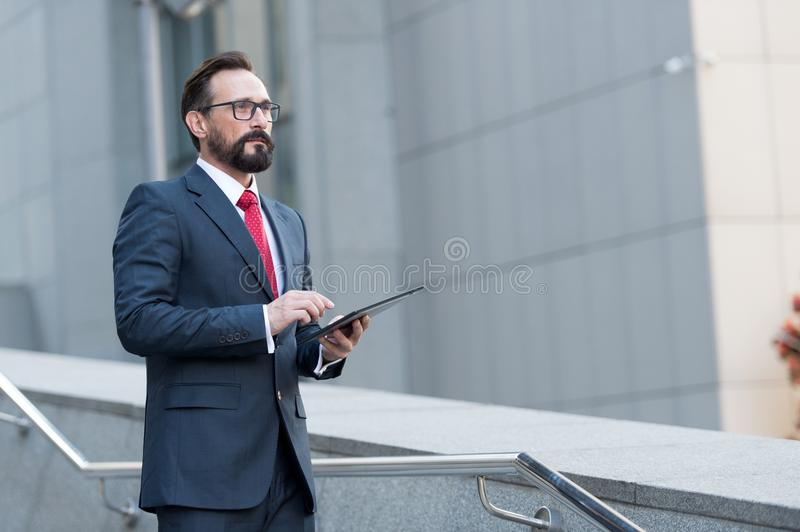 Bearded professional man broker standing outdoor while holding digital tablet in his hands. Modern businessman thinking overview royalty free stock photography