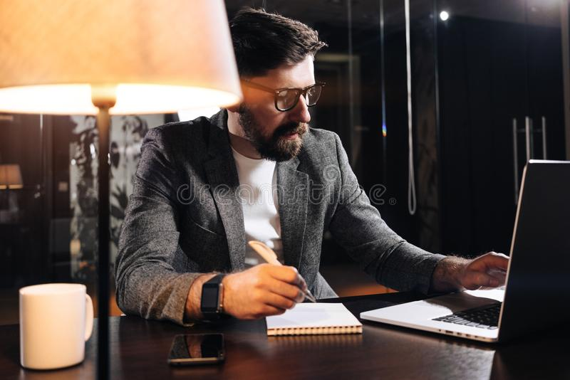 Bearded project manager hold pen in hand and using contemporary notebook. Young businessman working in loft office at night royalty free stock photography