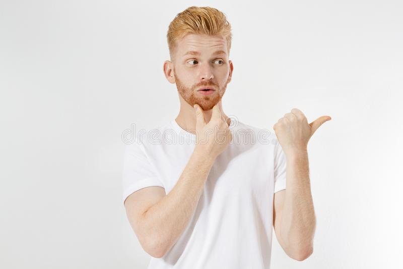Bearded red-haired smile man in white tshirt pointed to blank background copy space isolated over white royalty free stock photo