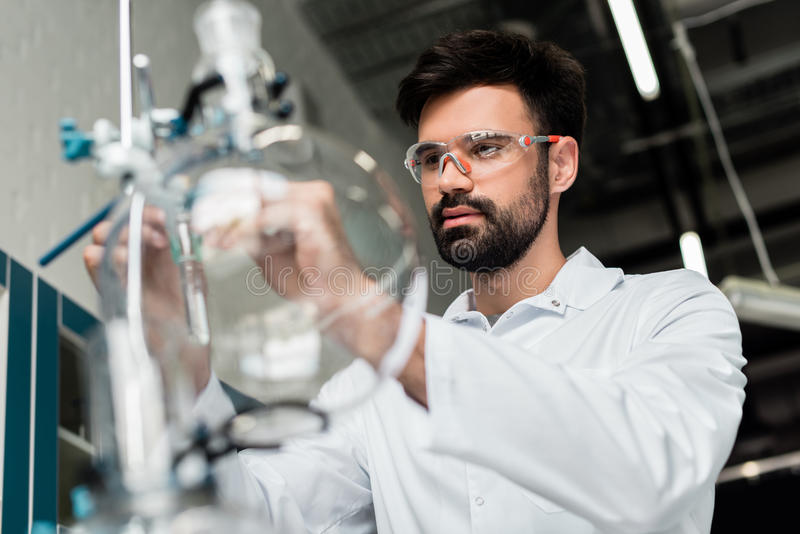 Bearded scientist in protective eyewear making experiment in laboratory. Concentrated bearded scientist in protective eyewear making experiment in laboratory royalty free stock photos