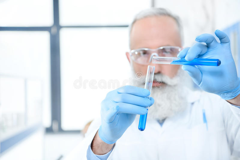 Bearded scientist in protective goggles and gloves holding test tubes with reagents and making experiment. Serious bearded scientist in protective goggles and stock photos