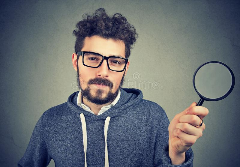 Curious man investigating with magnifier royalty free stock images