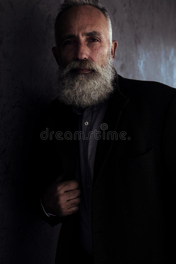 Bearded senior man in coat posing in dark studio background look stock images