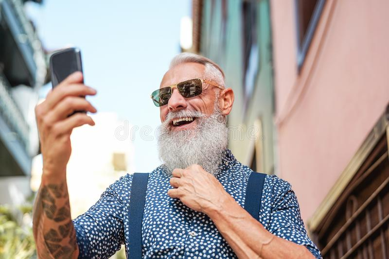 Bearded senior using mobile phone outdoor - Hipster mature man having fun with new trends smartphone apps stock image