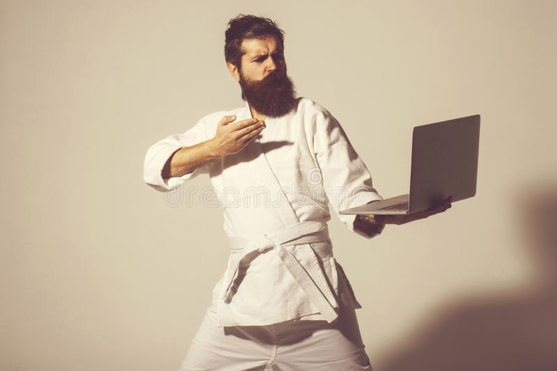 Bearded serious karate man in kimono with laptop. Bearded karate man, long beard, brutal caucasian hipster with moustache in white kimono holds laptop with royalty free stock images