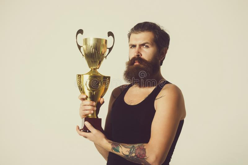 Bearded serious man holds gold champion cup on grey background. Bearded man, long beard, brutal caucasian hipster with moustache in black vest holds gold royalty free stock photo