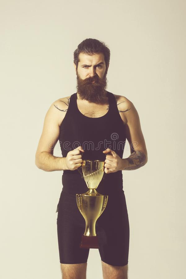 Bearded serious man holds gold champion cup on grey background. Bearded man, long beard, brutal caucasian hipster with moustache in black vest holds gold royalty free stock images
