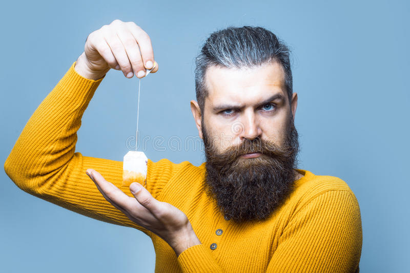 Bearded serious man with tea bag royalty free stock photography