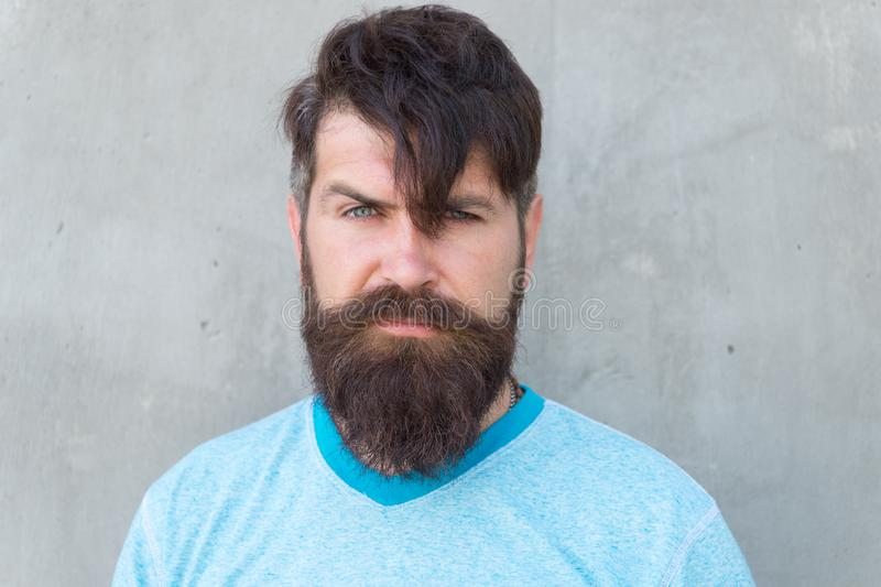 Bearded and shaggy. Bearded man with stylish haircut on grey wall. Unshaven caucasian guy wearing thick mustache and stock photo