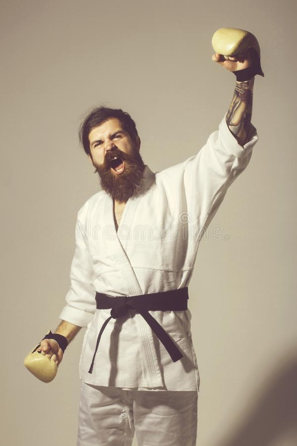 Bearded shouting happy karate man in kimono and boxing gloves royalty free stock photo