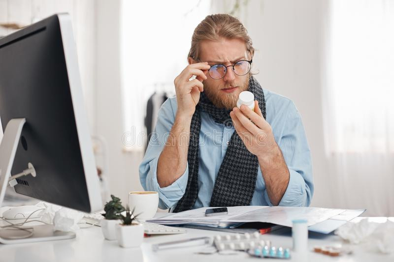 Bearded sick male office worker with spectacles on reads prescription of medicine. Young manager has bad cold, sits at stock photo