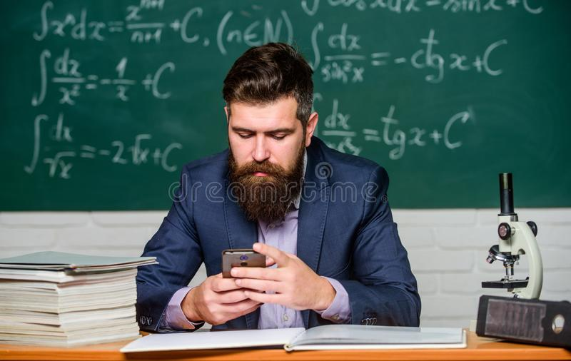 Bearded and smart. Man bearded hold smartphone. Bearded teacher or businessman read sms. Hipster with bearded face use stock photo