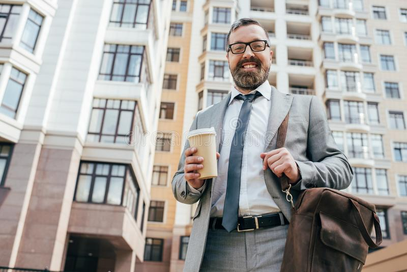 bearded smiling businessman in suit with leather bag holding coffee stock image