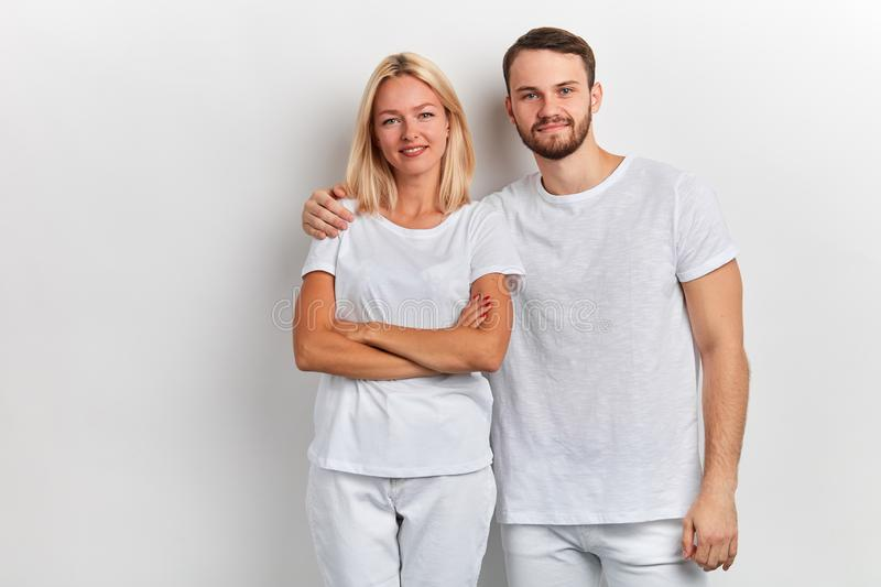Bearded smiling handsome man hugs a woman by the shoulder on a white background stock photos