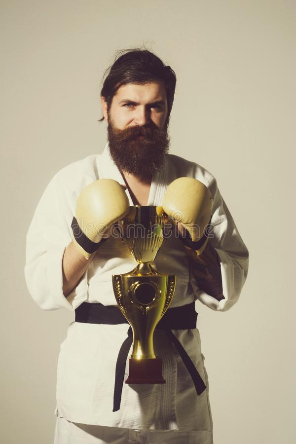 Bearded smiling karate man in kimono, boxing gloves, champion cup. Bearded karate man, long beard, brutal caucasian hipster with moustache in white kimono with royalty free stock photos