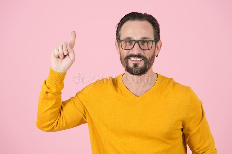 Bearded smiling man in glasses pointing up on pink background. Happy sales manager with finger up. Wise Man in glasses notices royalty free stock photography