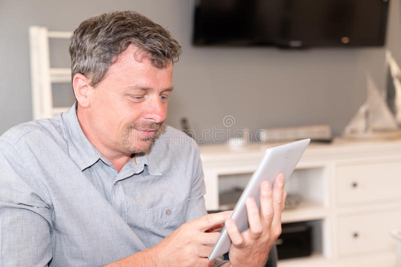 Bearded smiling man using tablet for video conversation while relaxing on sofa in modern house in Concept of business people stock photography