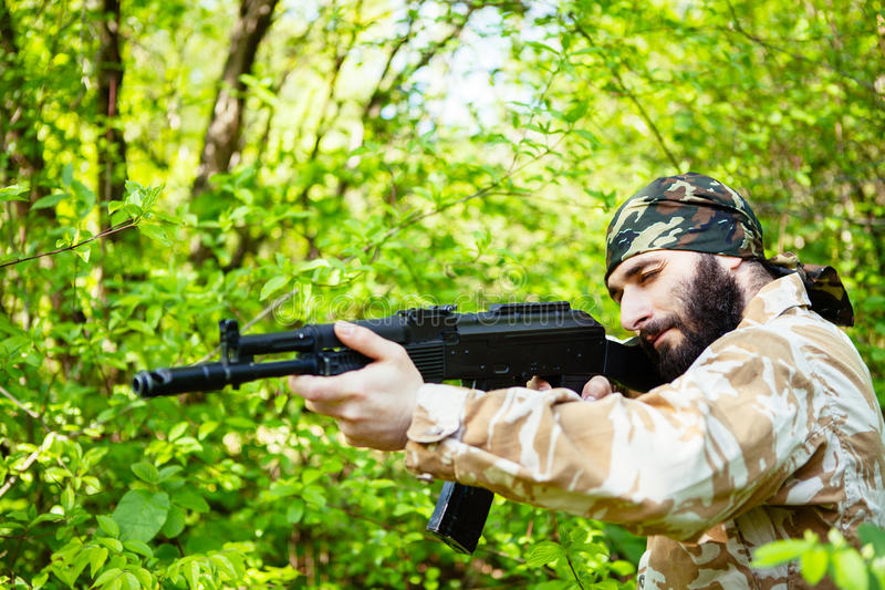 Bearded soldier with a rifle in the woods royalty free stock photo