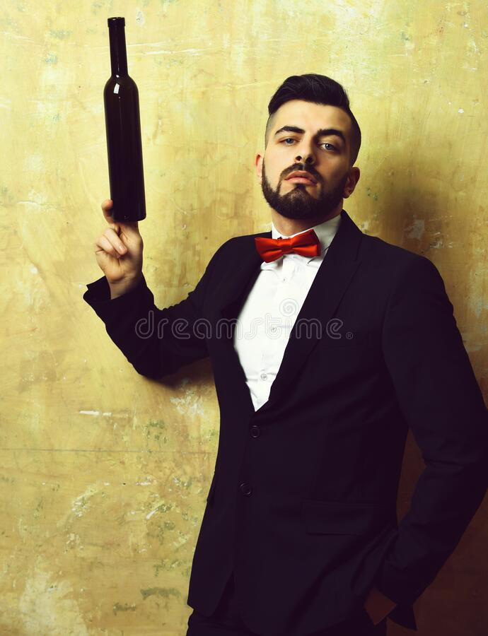 Bearded sommelier with confident face expression holds bottle of wine stock photo