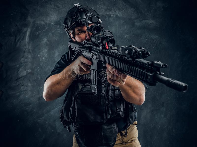Special forces soldier wearing body armor and helmet with night vision holding an assault rifle. Studio photo against a royalty free stock photography