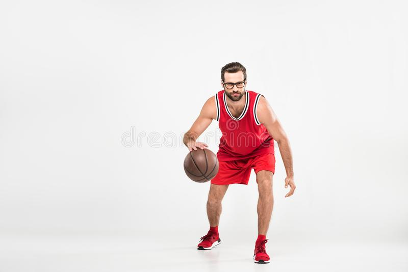 bearded sportsman in red sportswear and retro glasses playing basketball, royalty free stock photos