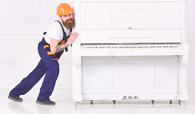 Bearded strong man bending while trying to move heavy piano with open keyboard and glass vase. Smiling guy in orange. Helmet over white background royalty free stock images