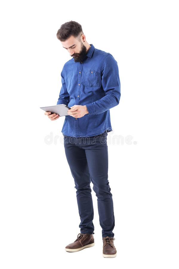 Bearded stylish business man holding tablet in both hands reading ebook. stock photo