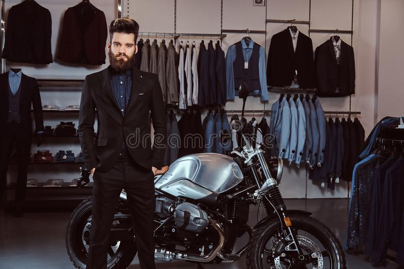 Bearded stylish man dressed in black suit posing with hands in pockets near retro sports motorbike at the men`s clothing royalty free stock image