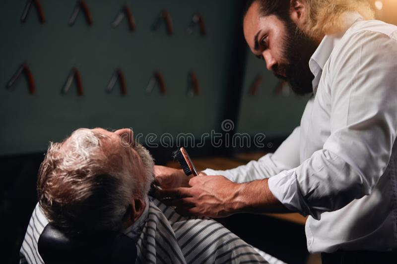Bearded stylist brusing the hair of his client. Close up side view photo royalty free stock photos