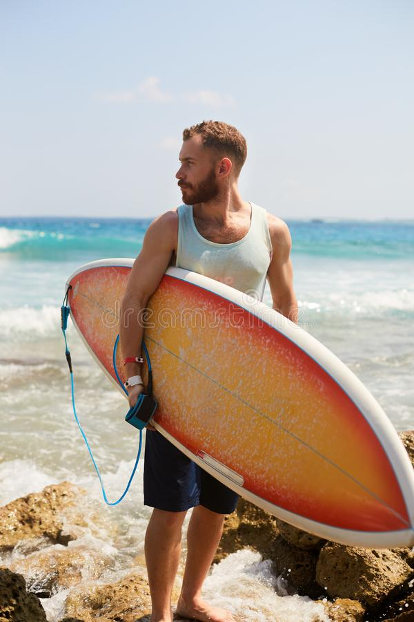 Bearded surfer with a surfboard is walking on the beach and watching for the waves on the spot stock image