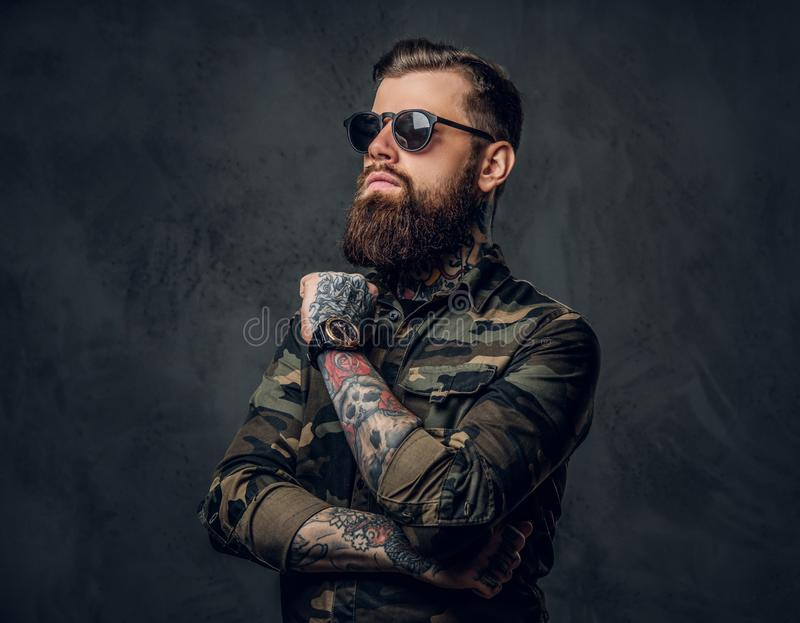 Bearded tattooed guy in military shirt and sunglasses posing with thoughtful look. Studio photo against dark wall stock image