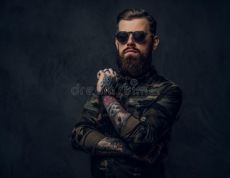 Bearded tattooed guy in military shirt and sunglasses posing with thoughtful look. Studio photo against dark wall stock photography