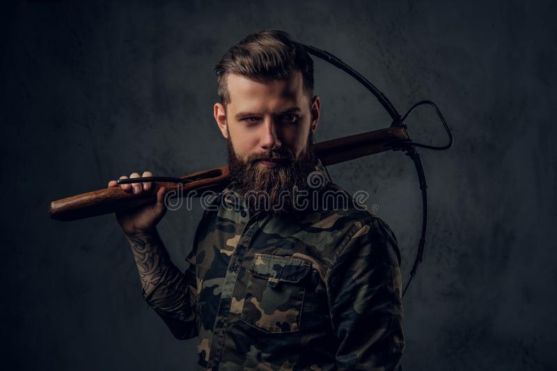 A bearded tattooed hipster guy in military shirt posing with a medieval crossbow. Studio photo against dark wall royalty free stock photos