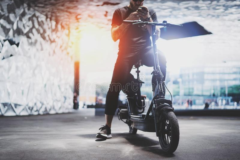 Bearded tattooed male in sunglasses using smartphone after riding by electric scooter in the city. stock photography
