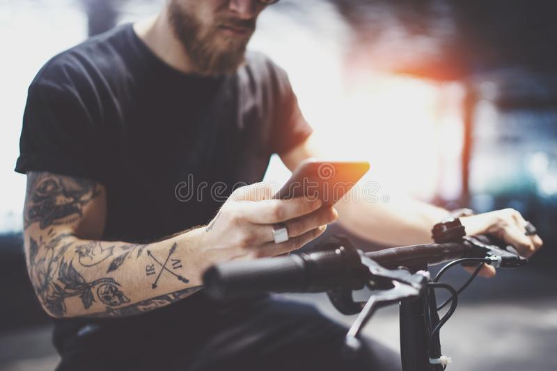 Bearded tattooed man in sunglasses using mobile phone for send text message after riding by electric scooter in the city royalty free stock photography