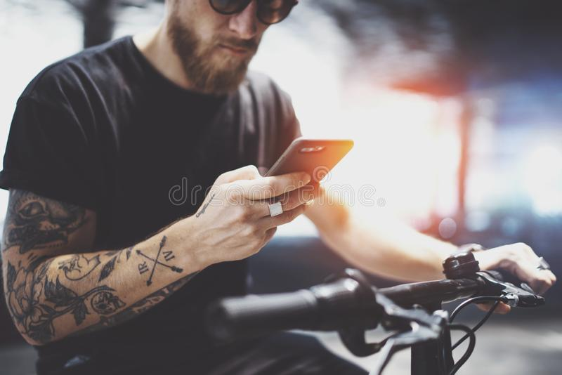 Bearded tattooed man in sunglasses using mobile phone for send text message after riding by electric scooter in the city stock photo